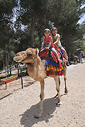 Two girls enjoy a camel ride, Negev, Israel