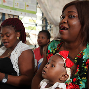 INDIVIDUAL(S) PHOTOGRAPHED: From left to right: Unknown, unknown, unknown, and unknown. LOCATION: Epko Abasi Clinic, Calabar, Cross River, Nigeria. CAPTION: In the waiting room of Epko Abasi clinic, a mother and her child wait to receive care.