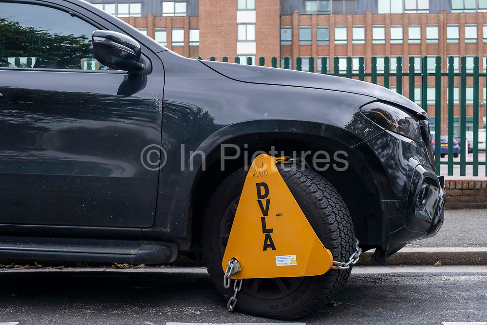 A bright yellow DVLA wheel clamp on a vehicle in a side street on the 15th of July 2021 in Folkestone, United Kingdom. The DVLA use automatic number plate readers to locate untaxed vehicles on the streets and clamps them until tax and fines have been paid. A clamped vehicle cannot be moved until it is removed.