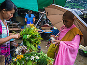 14 JUNE 2013 -  PANTANAW, AYEYARWADY, MYANMAR: A Buddhist nun buys flowers in the rain in the market in Pantanaw, in the Ayeyarwady Region of south-west Myanmar. It is the hometown of former United Nations Secretary-General U Thant and of the renowned artist U Ba Nyan.   PHOTO BY JACK KURTZ