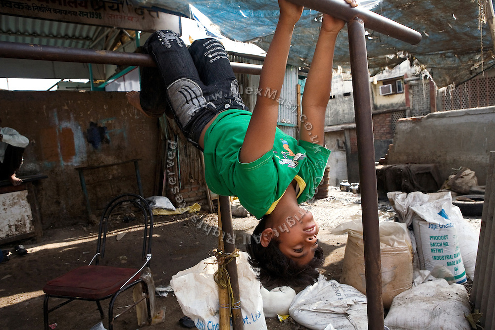 Azharuddin Ismail, 10, the child actor playing the role of 'young Salim', the brother of Jamal, protagonist of Slumdog Millionaire, the famous movie winner of 8 Oscar Academy Awards in December 2008, is exercising in the slum where he still lives with his family next to the train station of Bandra (East), Mumbai, India. Various promises were made to lift the two young actors (Azharuddin Ismail and Rubina Ali) from poverty and slum-life but as of the end of May 2009 anything is yet to happen. Rubina's house was recently demolished with no notice as it lay on land owned by the Maharashtra train authorities and she is now permanently living with her uncle's family in a home a stone-throw away in the same slum. Azharuddin's home too was demolished in the past two weeks, as it happens every year in his case, because the concrete walls were preventing local authorities to clear a drain passing right behind it. As usual, his father is looking into restoring the walls as soon as the work on the drain has been completed.