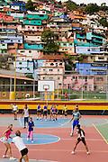 Girls and two men play volleyball in the 12 de Octubre barrio in Caracas, Venezuela.