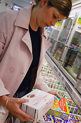 Young woman shopping economically by comparing and choosing supermarket brands,