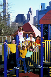 Stock photo of a group of children playing on a jungle gym at a park near downtown