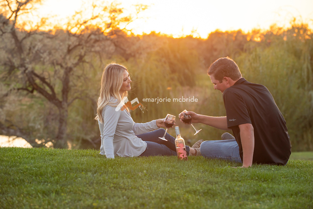 Cute couple enjoy wine while sitting in grass near a pond during sunset at Holeinsky Vineyard and Winery in Buhl, Idaho.