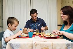 Polish family sitting around table eating dinner,