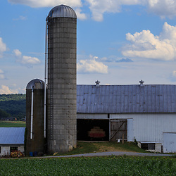 Strasburg, PA / USA - June 27, 2017:  A large white barn with two silos in rural Lancaster County, Pennsylvania.