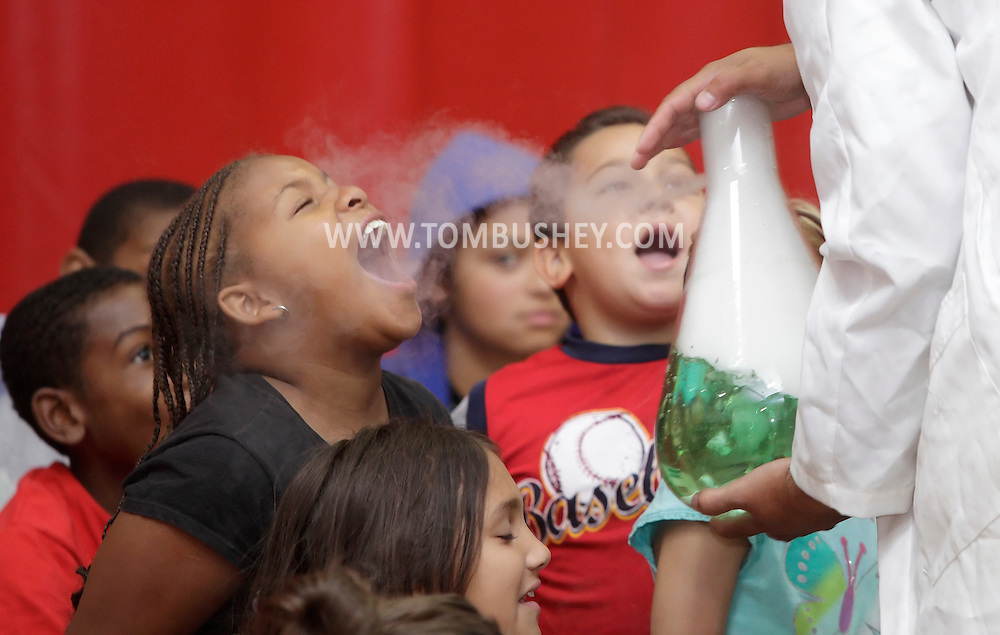 Middletown, New York - Erik Maldonado, right, directs a stream of carbon dioxide gas from a beaker full of water and dry ice at a camper during a Mad Science demonstration at Middletown YMCA summer camp on Aug. 20, 2010.
