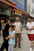 Zhou Futian photographed in Dazhalan - a busy shopping street - in front of the place where the shoe shop he was working for on October 1949 was located. Today the shoe shop still exists and has moved two doors down the street.