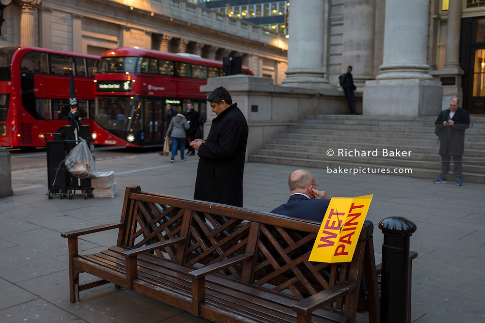 A businessman holds a conversation in the noisy city while also ignoring a Wet Paint sign, on 16th February 2017, outside Royal Exchange and the WW1 memorial, in the City of London, England.