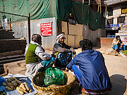 05 MARCH 2017 - KATHMANDU, NEPAL: A produce vendor chats with friends in front of tin wall blocking off a construction site for a building destroyed in the 2015 earthquake. Much of Kathmandu is now a construction site because of rebuilding  two years after the earthquake of 25 April 2015 that devastated Nepal. In some villages in the Kathmandu valley workers are working by hand to remove ruble and dig out destroyed buildings. About 9,000 people were killed and another 22,000 injured by the earthquake. The epicenter of the earthquake was east of the Gorka district.     PHOTO BY JACK KURTZ