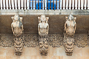 Ancient stone mythical maidens and gargoyles on Palazzo Nicolaci di Valladorata in Baroque Noto city, Sicily