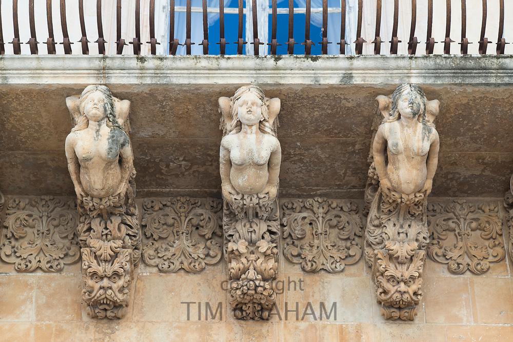 Ancient stone mythical maidens and gargoyles on Palazzo Nicolaci di Valladorata in Baroque Noto city, Sicily