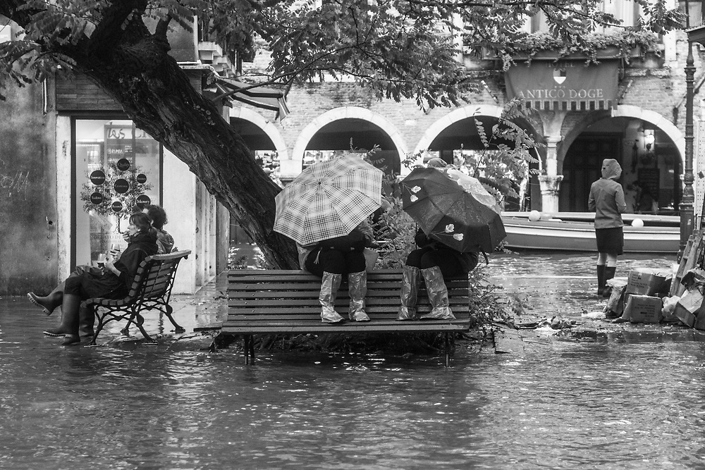 Venice, Italy. 29 October, 2018.  Tourists and citizen are sat on benches during the high tide in Castello district on October 29, 2018, in Venice, Italy. This is a selection of pictures of different areas of Venice that the press has not covered, were resident live and every year they have to struggle with the high tide. Due to the exceptional level of the 'acqua alta' or 'High Tide' that reached 156 cm today, Venetian schools and hospitals were closed by the authorities, and citizens were advised against leaving their homes. This level of High Tide has been reached in 1979. © Simone Padovani / Awakening / Alamy Live News