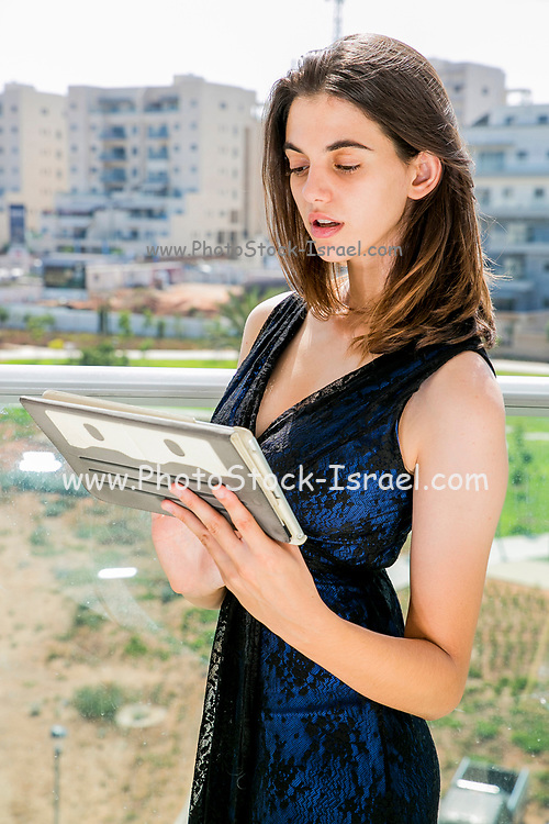 Young woman in formal dress works on her tablet on the balcony of her home