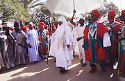 The Emir of Kano changes his horse and outfiut for each day and ceremon during the Fantasia Durbar at Kano..The Durbar Fantasia, is the moment where The Husa residents of Kano wear traditional dress, their local leaders and chiefs mount horses, and together with their militias display allegiance and homage to their leader, the Emir of Kano. This takes place after Ramadan. The Emir is Kano's State official political and economic feudal leader, everyone seeks to be in his pleasure, otherwise they reap the consequences..Kano is the largest Muslim Husa city, under the feudal, political and economic rule of the Emir. Kano and the other eleven northern states are under Islamic Sharia Law which is enforced by official state apparatus including military and police, Islamic schools and education, plus various volunteer Militia groups supported financially and politically by the Emir and other business and political bodies. 70% of the population live below the poverty line. Kano, Kano State, Northern Nigeria, Africa