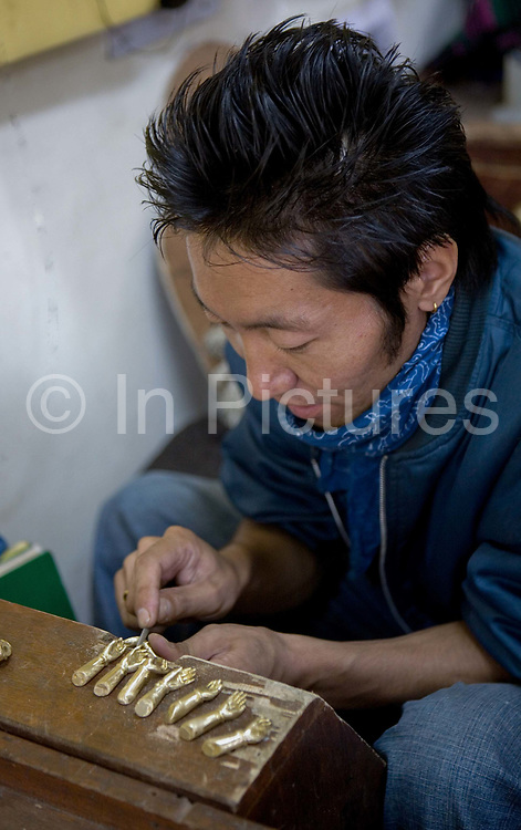 Artisans at the Tibetan Handicrafts Centre on 2nd November 2009, Mcleod Ganj, Dharamshala, state of Himachal Pradesh, India. Tibetan craftsmen artisans in exile live and work here, making traditional relgious iconography and handicrafts.