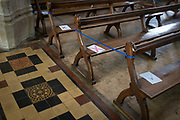 Church seating pews are marked with ticks and crosses marking where parishioners are allowed to sit according to Coronavirus pandemic lockdown guidelines in St. Peter and St. Pauls church, on 9th July 2020, in Lavenham, Suffolk, England. At the moment, indoor religious gatherings are still banned though private prayer is allowed. Completed in 1525, the church is excessively large for the size of the village and with a tower standing 141 ft 43 m high it lays claim to being the highest village church tower in Britain.