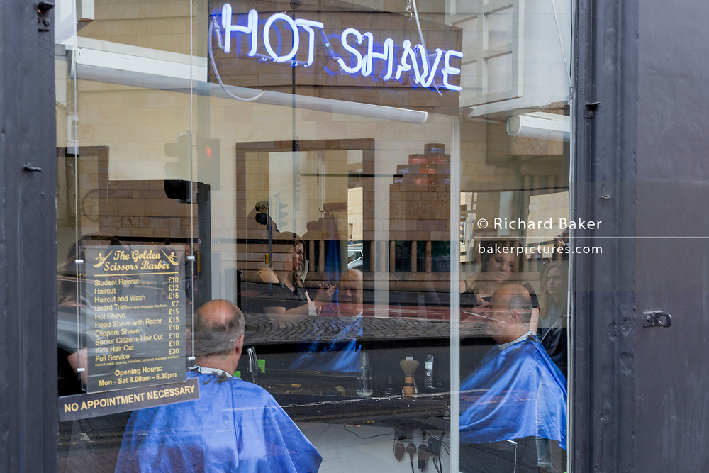 A balding middle-aged man sits in a barber's chair for a window haircut in Edinburgh, on 25th June 2019, in Edinburgh, Scotland.