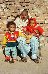 Woman sitting on chair at side of road with two young children wearing woollen jumpers,