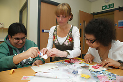 Carer assisting a group in craft activity at a resource for people with physical and sensory impairment.