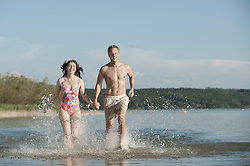 Mature couple running through the water in lake, Bavaria, Germany