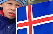 Young fair-haired boy holding the flag of Iceland