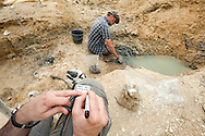 Comic strip artist Mazan writes an identification label for Ronan Allain, Head of Conservation of the reptile and bird fossil collections at the Natural History Museum in Paris. Palaeontological excavations at Angeac, Charente, France (July 2016) © Rudolf Abraham
