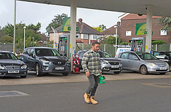 © Licensed to London News Pictures 28/09/2021.<br /> Mottingham, UK, This man walked to the station with a Jerry can and was the first to fill up. A tanker has just delivered fuel to Mottingham BP station in South East London. Within minutes of the tanker arriving motorists started to queue blocking roads. Chaos at the forecourts as people start to panic buy petrol. BP has started to ration petrol and diesel due to a shortage of truckers. Photo credit:Grant Falvey/LNP