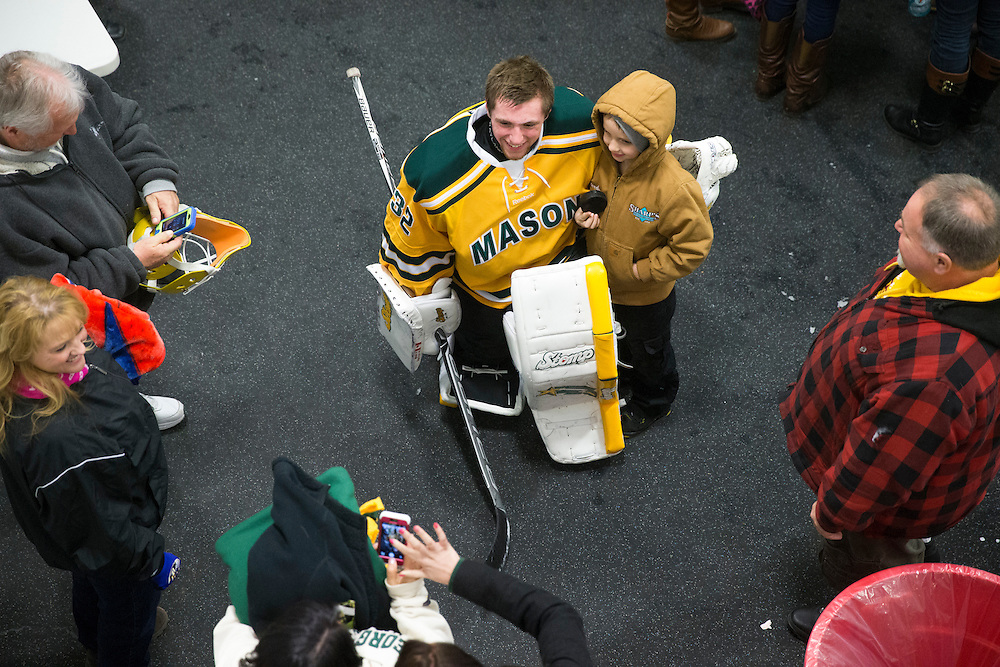 George Mason backup goalie, Nick Wayland, takes photos with friends and family after beating Northern Virginia Community College 18-1 on senior night at Prince William Ice Rink in Woodbridge, VA on January 31, 2014.