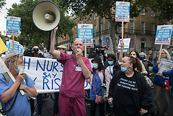 London, UK. 30th July, 2021. Staff nurse David Carr addresses NHS staff who marched from St Thomas' Hospital and UCH to Downing Street to protest against the NHS Pay Review Body's recommendation of a 3% pay rise for NHS staff in England. The protest march was supported by Unite the union, which has called on incoming NHS England Chief Executive Amanda Pritchard to ensure that a NHS pay rise comes from new Treasury funds rather than existing NHS budgets and which is shortly expected to put a consultative ballot for industrial action to its members.