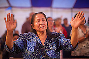 "13 JULY 2012 - FT DEFIANCE, AZ: A woman prays during the Friday night service at the 23rd annual Navajo Nation Camp Meeting in Ft. Defiance, north of Window Rock, AZ, on the Navajo reservation. Preachers from across the Navajo Nation, and the western US, come to Navajo Nation Camp Meeting to preach an evangelical form of Christianity. Evangelical Christians make up a growing part of the reservation - there are now more than a hundred camp meetings and tent revivals on the reservation every year. The camp meeting in Ft. Defiance draws nearly 200 people each night of its six day run. Many of the attendees convert to evangelical Christianity from traditional Navajo beliefs, Catholicism or Mormonism. ""Camp meetings"" are a form of Protestant Christian religious services originating in Britain and once common in rural parts of the United States. People would travel a great distance to a particular site to camp out, listen to itinerant preachers, and pray. This suited the rural life, before cars and highways were common, because rural areas often lacked traditional churches. PHOTO BY JACK KURTZ"