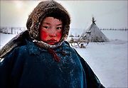 At home in the snow, a Nentsy boy stands near his chum, a tepee shelter made of reindeer hide. Soviet officials tried to organize the Nentsy and other Siberian tribes in to collectivized work units, but the Nentsy of the Yamal Peninsula continue in their nomadic ways, migrating across the tundra more than 600 miles, or a thousand kilometers, a year. © Steve Raymer / National Geographic Creative