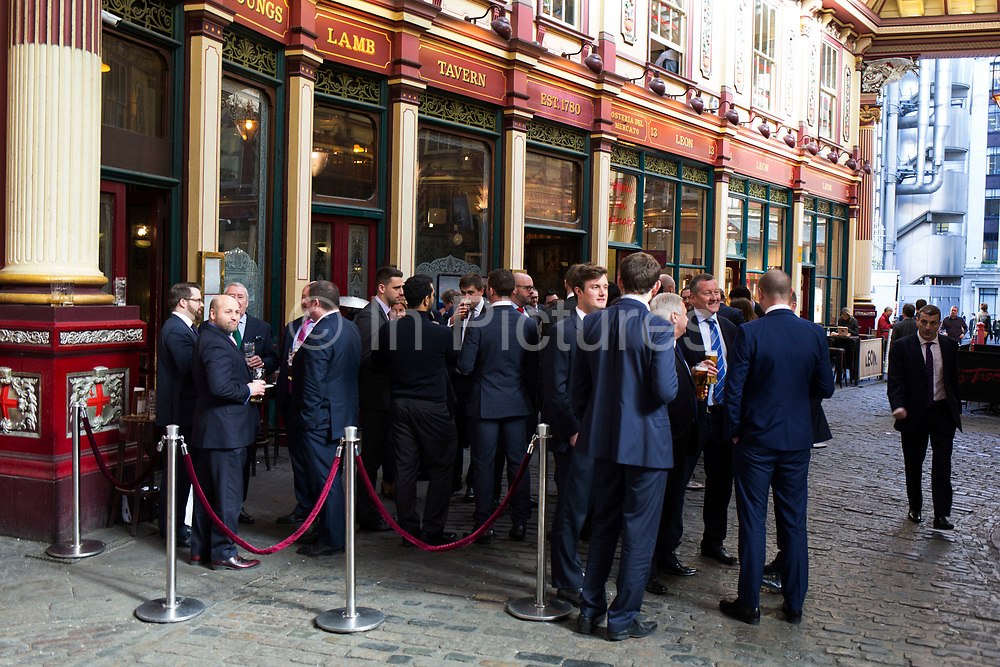 City workers enjoying an after work pint outside the Lamb Tavern pub in Leadenhall Market in the City of London, England, United Kingdom.