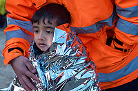 LESVOS, GREECE - FEBRUARY 09: A volunteer comforts a young boy wrapped in a thermal blanket after his arrival on a beach in South Lesvos with other refugees and migrants from the Turkish coast on February 09, 2015 in Lesvos, Greece. Photo: © Omar Havana. All Rights Are Reserved