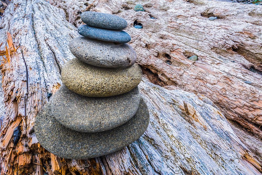 Rock cairn and driftwood, Strait of Juan de Fuca, Dungeness National Wildlife Refuge, Washington. USA