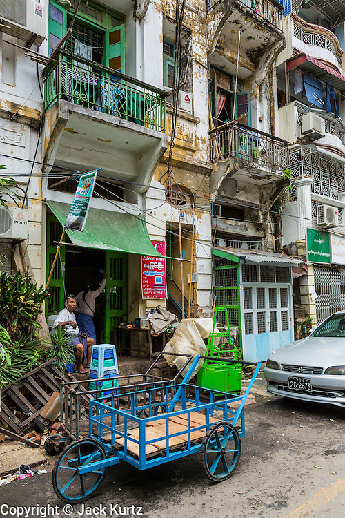 07 JUNE 2014 - YANGON, MYANMAR:  A residential building with shops on the ground floor on 22nd Street in Yangon. The building is one of a number of small colonial era buildings still in use in Yangon. This building, which doesn't have a name was opened in 1926. Yangon has the highest concentration of colonial style buildings still standing in Asia. Efforts are being made to preserve the buildings but many are in poor condition and not salvageable.   PHOTO BY JACK KURTZ