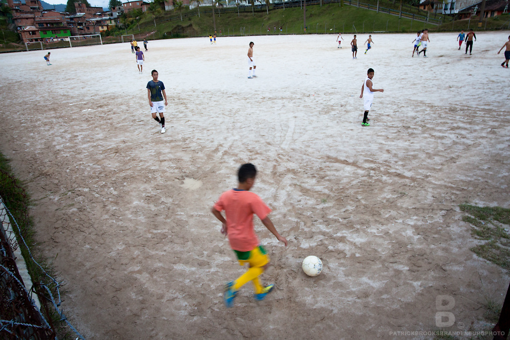 Kids play soccer on a stone white field in Guatape, Colombia.