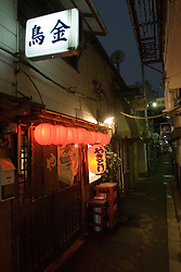 Night view of small bar with red lanterns in Golden Gai district of Shinjuku in Tokyo Japan