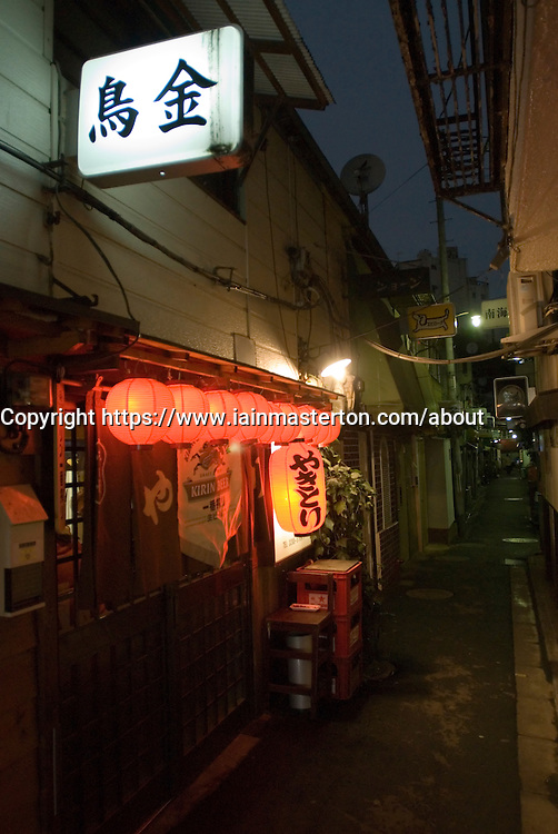 Night view of small bar with red lanterns in Golden Gai district of Shinjuku in Tokyo Japan