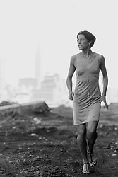 African American Woman walking on dirt in New Jersey ( across from the Empire State Building)