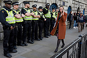 As environmental activists protest at Bank in the City of London, a City worker on her lunch hour passes a line of police officers on the 11th and final day of protests, road-blockages and arrests across London by the climate change campaign Extinction Rebellion, on 25th April 2019, in London, England.