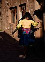 TAQUILE ISLAND, PERU - CIRCA OCTOBER 2015: Woman webing wool and walking in the strets of Taquile Island, in Lake Titicaca, Peru.