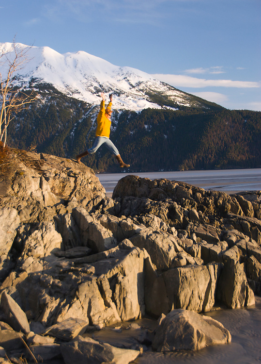Alaska. Turnagain Arm, Chgach State Park. A woman hiker jumps over a rock.