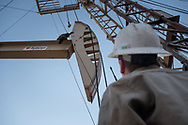 Oil field workers with Wisco work on a rig in Tioga, N.D., Nov 6, 2013. Back in 2008 the North Dakota oil boom started its ongoing period of extraction of oil from the Bakken formation. The amount of jobs the oil boom has provided North Dakota has helped give it the lowest unemployment rate in the United States and and gave it a billion dollar surplus.  Photo Ken Cedeno