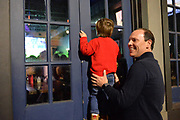 3/5/21 Oxford MS. Oxford, Mississippi, USA: Michael Henry of Jackson Mississippi holds his 3yr old son up to the window of a bar in Oxford so he can get a better view of whats going on inside. The Henry family came up to watch the baseball game and said they hadn't been out in months and it was fantastic to be without a mask. March 5, 2021, Students of The University of Mississippi, aka, Ole Miss, party and enjoy a night out on the first Friday night after Governor Tate Reeves lifted the state wide mask mandate. The bars in downtown Oxford were packed with students shoulder to shoulder drinking and partying. Dr Fauci has stated that Mississippi and Texas residents should continue to abide by public health measures, including wearing masks and social distancing, even as Republican Governors have lifted all Covid-19 restrictions in Texas and Mississippi. Photo© Suzi Altman