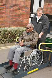 Bus driver on tailgate of specialised vehicle helping visually-impaired wheelchair user at a resource for people with physical and sensory impairment.