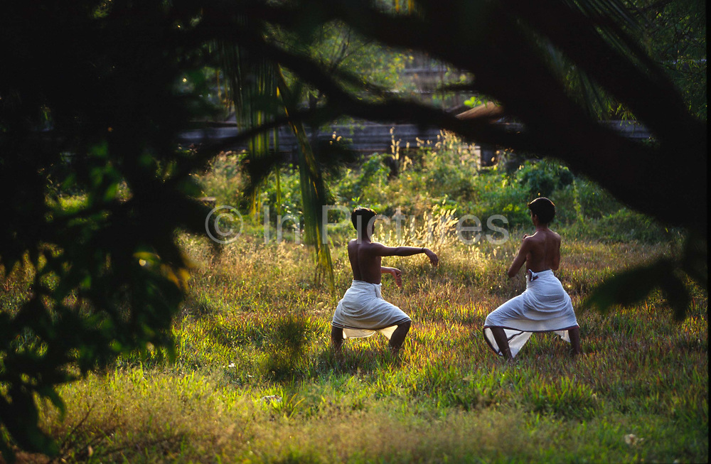 Students practice their dance steps in the gardens of the Kerala Kalamandalam.The Kalamandalam was founded in the 1930's to preserve the ancient forms of Keralan arts and dance of which Kathikali, a mute mixture of ballet and drama is the most well known..Cherathuruty, Kerala, India