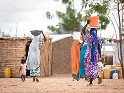 30 May 2019, Mokolo, Cameroon: Women carry their jerry cans homeward from one of the tapstands in Minawao camp. The Minawao camp for Nigerian refugees, located in the Far North region of Cameroon, hosts some 58,000 refugees from North East Nigeria. The refugees are supported by the Lutheran World Federation, together with a range of partners.