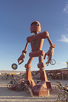 Becoming Human from: El Prado, NM year: 2015<br /> <br /> Becoming Human is a 30-foot tall sculpture of a robot, which occasionally smells the flower in its right hand. The sculpture hopes to inspire viewers to ask questions about technology and nature, and the value of slowing down. Contact: crobox@gmail.com
